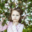 Beautiful blonde blue-eyed girl in a flowering apple orchard — Stock Photo #73606203