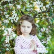 Beautiful blonde blue-eyed girl in a flowering apple orchard — Stock Photo #73606217