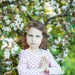 Beautiful blonde blue-eyed girl in a flowering apple orchard — Stock Photo #73606219