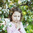 Beautiful blonde blue-eyed girl in a flowering apple orchard — Stock Photo #73606209