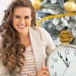 Smiling young woman showing clock near christmas tree — Stock Photo #59555443