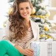 Portrait of happy young woman holding christmas present box — Stock Photo #59555491