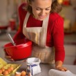 Happy young housewife making christmas cookies in kitchen — Stock Photo #59555725