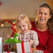 Portrait of smiling mother and baby opening christmas present bo — Stock Photo #59558369