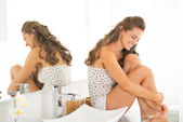 Happy young woman sitting in bathroom — Stockfoto