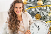 Smiling young woman showing clock near christmas tree — Stock Photo