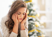 Portrait of stressed young woman near christmas tree — Stock Photo