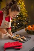 Young housewife decorating christmas cookies with pastry bag — Stock Photo