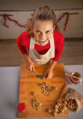 Portrait of happy young housewife chopping walnuts — Stock Photo