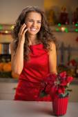 Portrait of happy young housewife talking cell phone in christma — Stock Photo