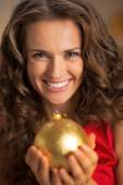 Portrait of smiling young housewife holding christmas ball — Stock Photo