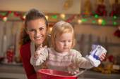 Portrait of flour smeared mother and baby making christmas cooki — Stock Photo