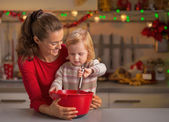 Happy mother and baby whisking dough in christmas decorated kitc — Stock Photo