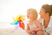 Mother and baby girl playing with colorful windmill toy on the b — Stock Photo