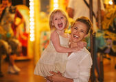 Portrait of smiling mother and baby girl in front of carousel — Stock Photo