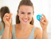 Closeup on happy young woman showing dental floss — Stock Photo