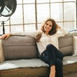 Relaxed young woman sitting on couch in loft apartment — Stock Photo #59635469