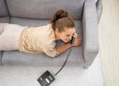 Young woman laying on divan in living room and talking phone — Stock Photo