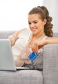Young housewife with credit card using laptop — Stock Photo