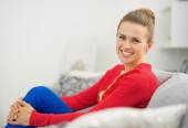 Portrait of happy young woman sitting on divan — Stock Photo