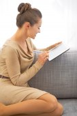 Young woman using tablet pc while sitting on divan — Stock Photo