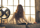 Young woman looking in window in loft apartment. rear view — Stok fotoğraf