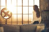 Young woman looking in window in loft apartment. rear view — Stock Photo