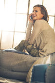 Happy young woman talking cell phone in loft apartment — Stock Photo