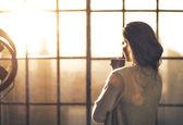 Mladá žena se těší šálek kávy v podkrovní byt. zadní pohled — Stock fotografie
