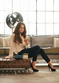 Jovem mulher escrever sms enquanto está sentado no apartamento loft — Fotografia Stock