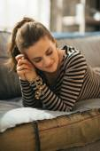 Relaxed young woman laying on divan in loft apartment — Stock Photo