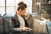 Business woman drinking coffee latte in loft apartment — Stockfoto