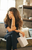 Frustrated young woman with letter in loft apartment — Photo