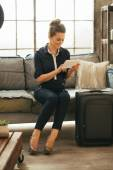 Young woman with luggage using tablet pc — Photo