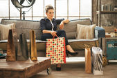 Relaxed young woman with shopping bags sitting in loft apartment — Stock Photo