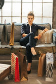 Young woman with shopping bags sitting in loft apartment — Stock Photo