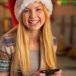 Happy teenager girl in santa hat writing sms — Stock Photo #59909111