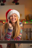Happy teenager girl in santa hat talking cell phone in christmas — Stock Photo