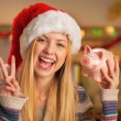 Happy teenager girl in santa hat showing victory gesture and pig — Stock Photo #59912345
