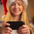Closeup on happy teenager girl in santa hat writing sms — Stock Photo #59914933