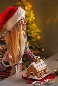 Happy teenager girl in santa hat decorating christmas cookie hou — Stock Photo