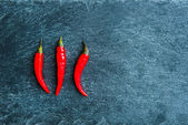 Closeup on red chili peppers on stone substrate — Stock Photo