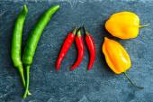 Closeup on mix of chili peppers on stone substrate — Stock Photo