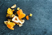 Closeup on mix of dried fruits on stone substrate — Stock Photo