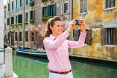 Happy young woman taking photo in venice, italy — Stock Photo
