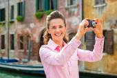 Smiling young woman taking photo in venice, italy — Stock Photo