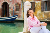 Portrait of smiling young woman sitting on street in venice, ita — Stockfoto