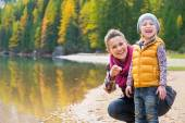 Portrait of smiling mother and baby on lake braies in south tyro — Stock Photo