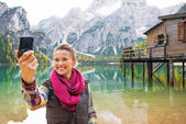 Happy young woman making selfie on lake braies in south tyrol, i — Stock Photo