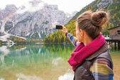 Young woman taking photo on lake braies in south tyrol, italy. r — Stock Photo